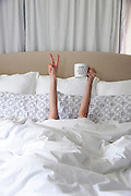 Woman rising out of bed with a cup of coffee.