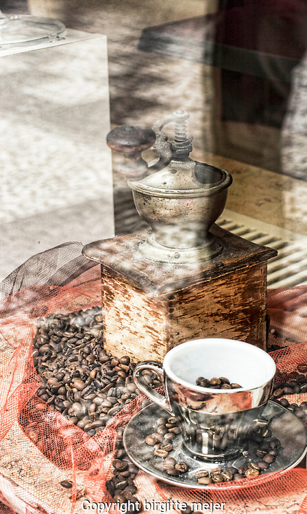 "Window display, with an old wooden Coffe Mill, Coffe Beans around it, and a ""silver"" coffee Cup with raw Beans inside. All placed on orange Tyl."