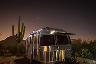 An Airstream camper trailer is outlined against the night sky at a campsite in Gilbert Ray campground in Tucson Mountain Park, Tucson, Arizona.