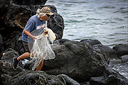 Brother Nolan walks on rocks checking fish thinking about throwing net on Molokai's east side. He did not throw net.