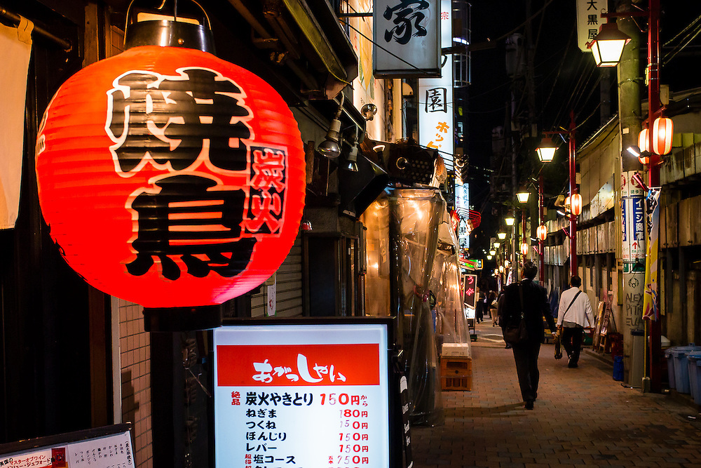 A red paper lantern marks the entrance to one of the many restaurants in an alley near Shinjuku Station