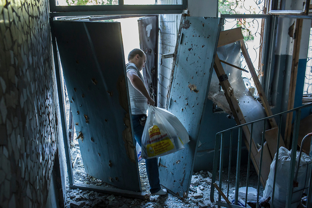 A resident of an apartment building hit by a suspected grad rocket strike evacuates with some of his belongings on Tuesday, July 29, 2014 in Donetsk, Ukraine.