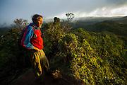 Robert Kuzy stands on the highpoint of the Pihea Trail looking down into Kalalau Valley, Kokee State Park, Kauai, Hawaii.