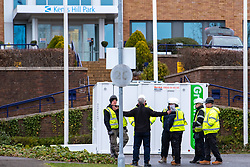 © Licensed to London News Pictures. 08/02/2020. Milton Keynes, UK. Contractors stand next to a portacabin at the entrance to the Kents Hill Park Conference Centre. A Milton Keynes conference centre is to house evacuees from the Chinese city of Wuhan, the epicentre of the Novel Coronavirus (2019-nCoV) outbreak, the British citizens are due to be flown back on Sunday 9th February and are expected to land at RAF Brize Norton in Oxfordshire and will remain at the Kents Hill Park Training and Conference Centre for 14 days to be monitored. Photo credit: Peter Manning/LNP