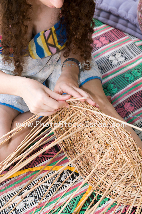 Young woman weaves a basket from reeds