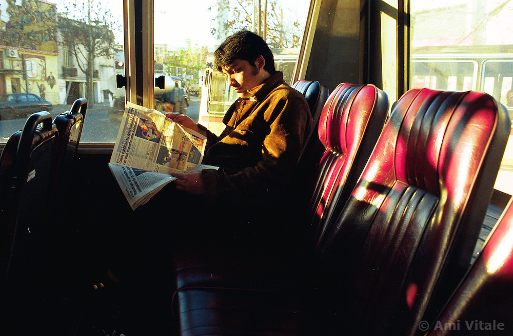 BUENOS AIRES, ARGENTINA: A man read the newspaper while on the bus in Buenos Aires, Argentina. .(Photo by Ami Vitale)