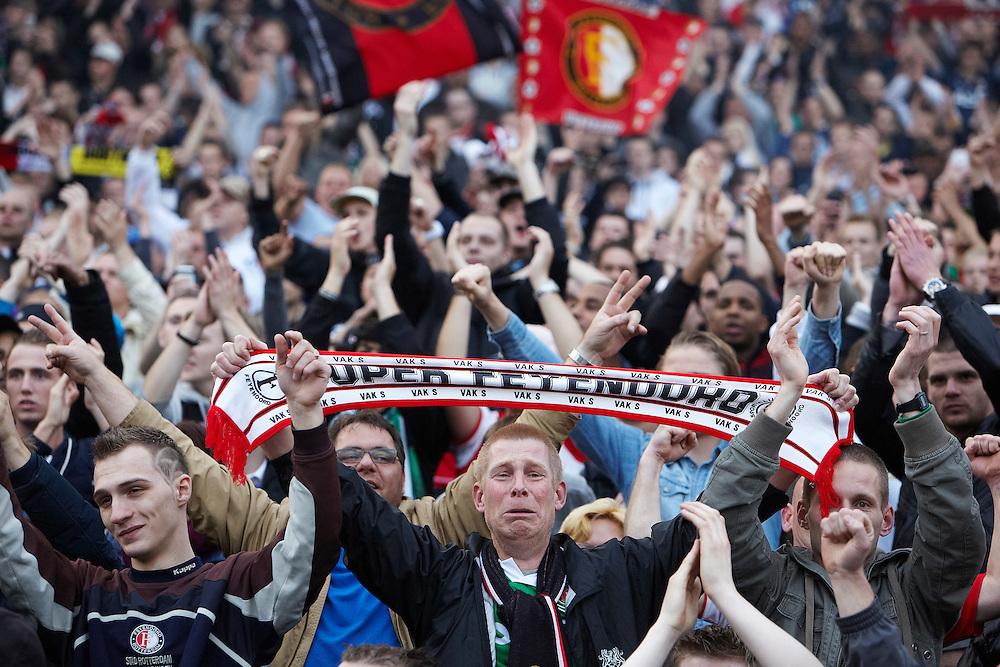 Nederland. Rotterdam, 6  mei 2012.<br /> Feyenoordsupporters vieren de overwinning op Heerenveen en het bereiken van de tweede plaats dat recht geeft op de  Champions League . Bij terugkeer in Rotterdam wordt de selectie gehuldigd in De Kuip, waar zo'n 30.000 mensen op de tribune zitten. voetbal, fan, fans, supporters, voetbalsupporters, Feyenoord, clubliefde, huilen, emotie, ontroering, emotioneel, juichen, vieren, feest, feestvieren,<br /> Foto : Martijn Beekman
