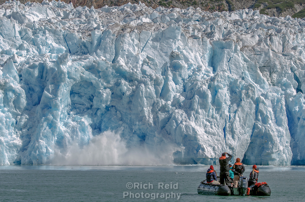 South Sawyer Glacier calving with zodiac in the foreground in Tracy Arm - Fords Wilderness in Southeast Alaska.