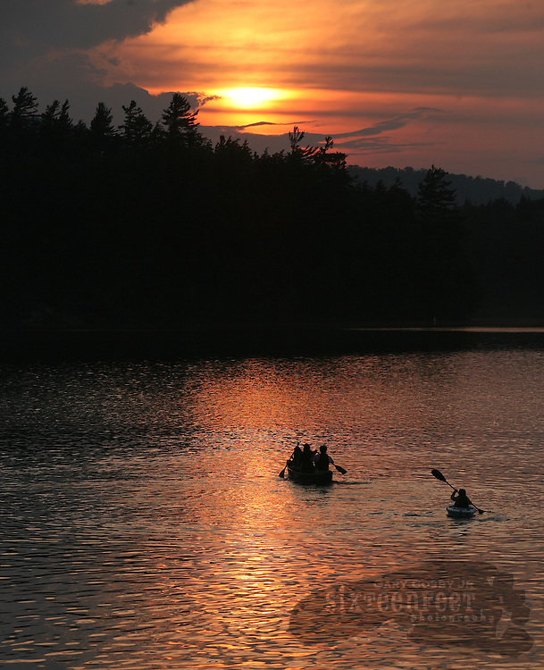 People in a canoe and a kayak paddle into the setting sun on Tupper Lake in Adirondack Park near Tupper Lake, New York.  Photo by Gary Cosby Jr.