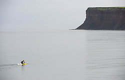© Licensed to London News Pictures. 19/06/2013<br /> <br /> Saltburn Beach, Cleveland, England, UK<br /> <br /> RNLI Lifeguard, Ritchie Mitchell paddles towards the cliffs on patrol at Saltburn by the Sea in Cleveland on what could be the hottest day of the year so far.<br /> <br /> Photo credit : Ian Forsyth/LNP