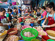 "05 APRIL 2014 - BANGKOK, THAILAND:   Women work in a fish processing business in Khlong Toey Market in Bangkok. Khlong Toey (also called Khlong Toei) Market is one of the largest ""wet markets"" in Thailand. The market is located in the midst of one of Bangkok's largest slum areas and close to the city's original deep water port. Thousands of people live in the neighboring slum area. Thousands more shop in the sprawling market for fresh fruits and vegetables as well meat, fish and poultry.     PHOTO BY JACK KURTZ"