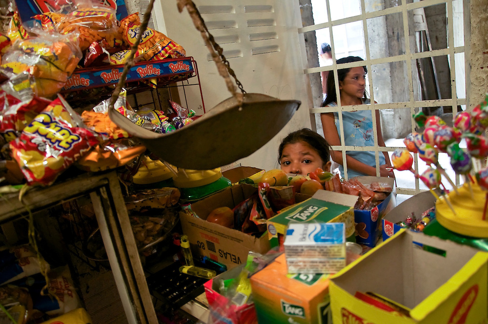 """A young girl helps her aunt attend to customers at the well-stocked bodega on the 7th floor of the """"Tower of David."""" Nearly each floor has it's own store where residents may purchase everything from fresh bread and milk, to cleaning supplies."""