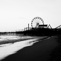 Santa Monica Pier black and white panroramic photo. Santa Monica Pier is a landmark that has an amusement park with a ferris wheel, roller coaster, restaurants, and other attractions. Panorama photo ratio is 1:3.
