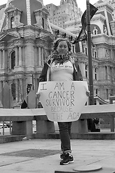 "Nora ""I AM A CANCER SURVIVOR BECAUSE OF THE ACA"" marches in protest at City Hall in Philadelphia, PA during the Trump-Congress retreat."