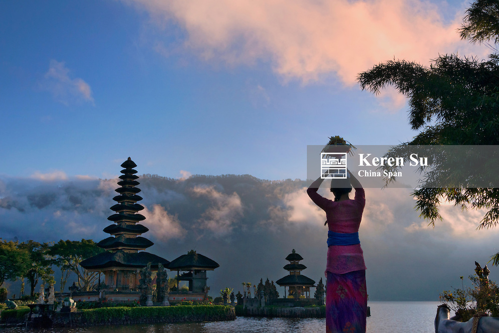 Girl carrying flower basket with Pura Ulun Danu Bratan water temple, Bali island, Indonesia