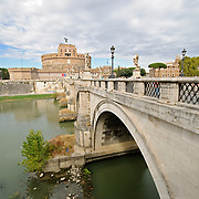 A shot of the historic jail, the Castel Sant' Angelo, from across the Tiber River with a bridge in the foreground in Rome, ITaly