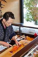 Mature Asian chef cutting fish in restaurant