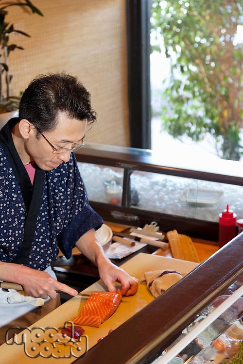 Mature Asian chef cutting fish in restaurant