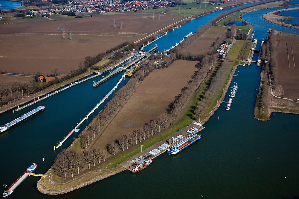 Nederland, Limburg, Gemeente Maasgouw, 07-03-2010; sluiscomplex Heel met links de dubbelsluis van het Lateraalkanaal. Links van het kanaal komt, na de sluis, een retentiegebied voor de opvang van (hoog) water. .De kleinere sluis (r) geeft toegang tot de Maas naar Roermond. Voor schepen naar het noorden biedt het kanaal een kortere en snellere route dan de oorspronkelijke Maasroute. De aanleg van het sluiscomplex zorgde er voor dat een enorme bocht in de Maas afgesneden kon worden (de Lus van Linne).Lock complex at Heel with double-lock for the Lateral canal (l). Left of the canal, after the lock, a retention area is created for the reception of (high) water..The smaller lock (r) provides access to the Maas to Roermond. For ships to the north, the channel offers a shorter and faster route than the original Maasroute. The construction of the lock complex cut of a huge bend in the Meuse(the Loop of Linne)..luchtfoto (toeslag), aerial photo (additional fee required);.foto/photo Siebe Swart