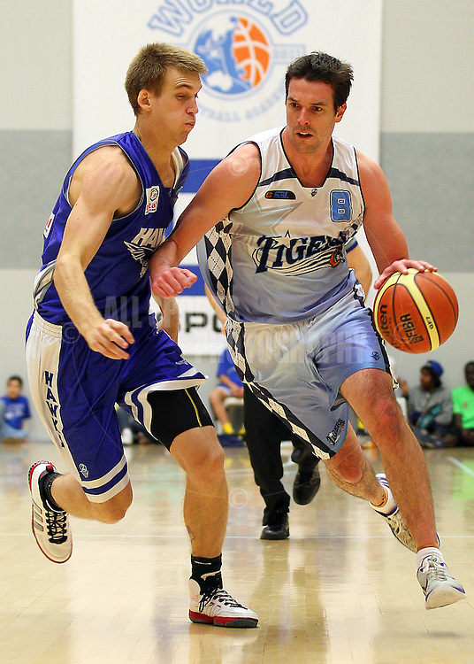 PERTH, AUSTRALIA - JULY 16: Ian Callaghan of the Tigers drives past Rory Pekin of the Hawks during the week 18 SBL game between the Perry Lakes Hawks and the Willetton TIgers at The State Basketball Center on July 16, 2011 in Perth, Australia.  (Photo by Paul Kane/Allsports Photography)