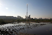 Waste from a factory submerges the land around it.