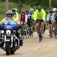 A Tupelo Police Department Motor Officer leads a group of bicyclists east on McCullough Blvd Thursday afternoon prior to their visit to the Elvis Presley Birthplace in Tupelo. The group of cyclists are traveling across the country on their way to Washington DC for National Police Week.