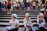 ROME, ITALY - OCTOBER 3: Moms breast feeding children, the Trinita dei Monti, during the World Week for the breastfeeding, organized  by the Movement Lactation Maternal Italian with the aim of promoting the benefits of breastfeeding on October 3, 2015 in Rome, Italy.