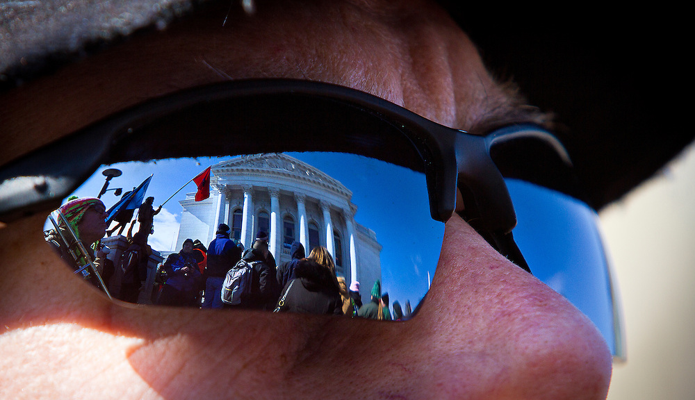 MADISON, WI — FEBRUARY 24: The Wisconsin State Capitol is reflected in the sunglasses of a rally supporter as workers and labor unions protested a right-to-work bill going through the state legislature.