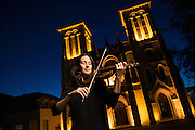 A violinist plays outdoors in San Antonio with a beautiful church as a backdrop.