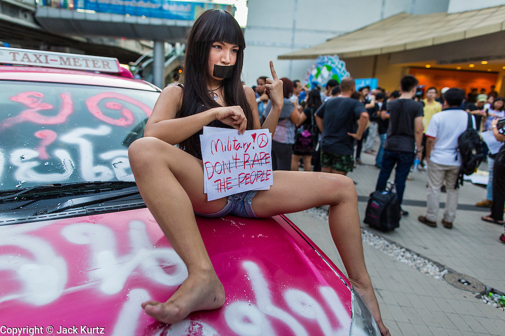 20 MAY 2014 - BANGKOK, THAILAND:  Saran Chuichai, aka Aum Neko, a well known Thai transgendered rights' protestor sits on a car after the coup and holds up a sign against martial during a pro-democracy vigil in Bangkok. About 200 Thais gathered at the Bangkok Art and Culture Centre in central Bangkok to protest the army's decision to impose martial law.   PHOTO BY JACK KURTZ