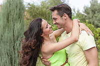 Side view of romantic young couple embracing in park