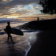 A surfer walks to shore after riding his last wave of the day as the sun sets on the west coast of Maui.