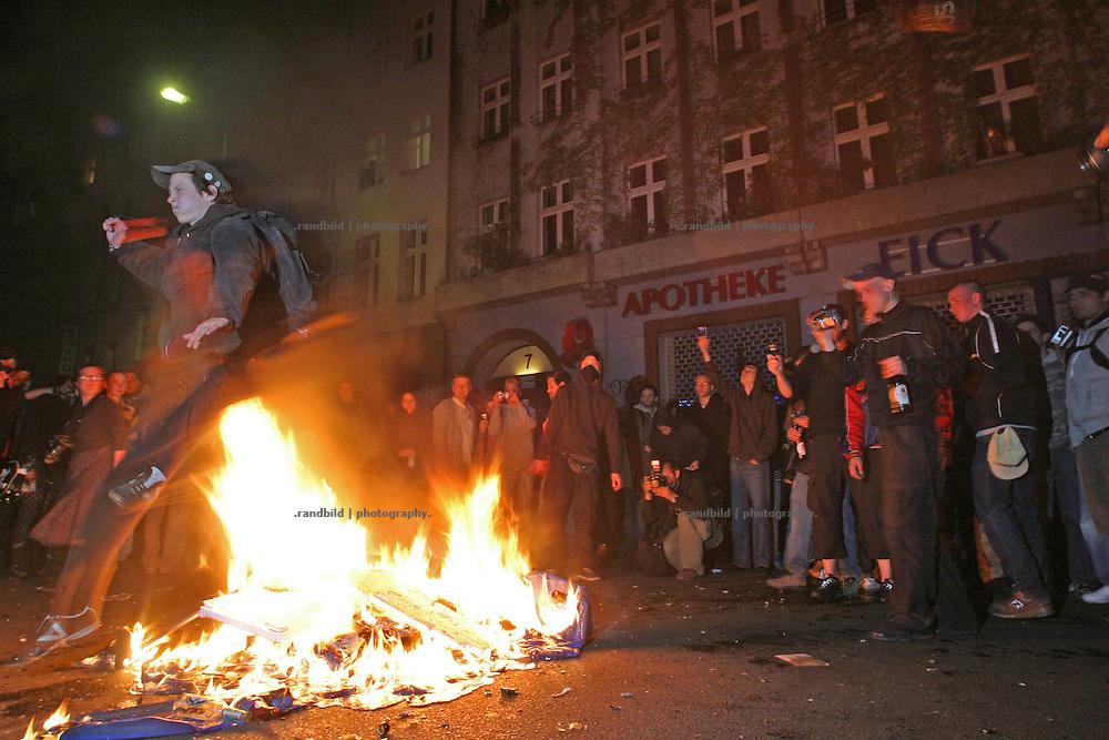 In Berlin-Kreuzberg springt ein Demonstrant während der Mai-Krawalle über einen brennenden Müllhaufen auf der Straße. A man jumps above a burning waste heap. It was part of the 1.May riots in Berlin-Kreuzberg