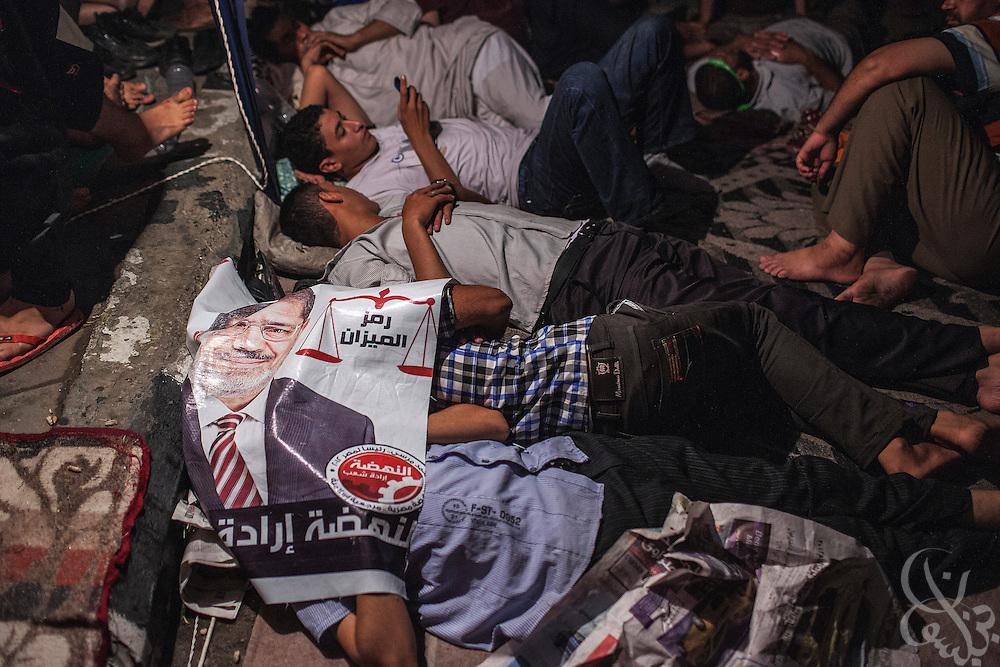 Pro-Morsi/anti-coup supporters sleep under a poster of deposed Egyptian president Mohamed Morsi following a day of marches Friday July 19, 2013 at the Rabaa al-Adawiya mosque in Nasr City. For 3 weeks, protesters angry with the decision of the military to remove Morsi from power have been camped out at the mosque by the thousands, and have vowed to remain until Morsi is returned to power.