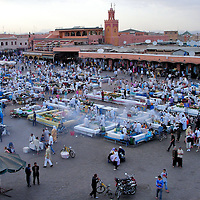 Jemaa el Fna at Dusk in Marrakech, Morocco<br /> The largest and most famous square in Marrakech began in the 11th century during the Almoravid Dynasty. They were rulers of Morocco from 1040 until 1147. The name of Jemma el Fna loosely translates to &ldquo;Meeting place of bliss or tranquility.&rdquo;  It does attract crowds but is far from tranquil.  By day, this UNESCO World Heritage Site is a menagerie of entertainers, musicians, belly dancers, acrobats, monkeys. henna tattoo artists and fortune tellers. At about 5:00 P.M., Djemaa el Fna transforms into a steaming banquet of cuisine served by food vendors.