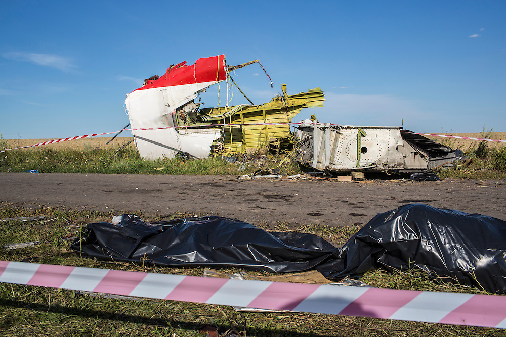 GRABOVO, UKRAINE - JULY 20: The bodies of victims of the crash of Malaysia Airlines flight MH17 await collection by the side of the road near a piece of the airplane on July 20, 2014 in Grabovo, Ukraine. Malaysia Airlines flight MH17 was travelling from Amsterdam to Kuala Lumpur when it crashed killing all 298 on board including 80 children. The aircraft was allegedly shot down by a missile and investigations continue over the perpetrators of the attack. (Photo by Brendan Hoffman/Getty Images) *** Local Caption ***