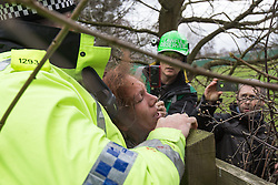 © Licensed to London News Pictures . 17/03/2014 . Barton Moss , Salford , UK . A woman with blood on her face is detained by police as protesters attempt to block lorries from accessing the iGas site . Happy Mondays dancer , Bez ( Mark Berry ) , joins protesters at the Barton Moss anti-fracking protest site in Salford today (Monday 17th March 2014) . Bez has said he will stand for MP in the constituency of Salford and Eccles in 2015 . Photo credit : Joel Goodman/LNP