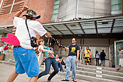 31 JULY 2010 - PHOENIX, AZ: Protesters dance the limbo in front of the 4th Ave Jail in Phoenix while they wait for their friends to be released Saturday morning. The last of the people arrested in Phoenix for protesting against Arizona's tough anti-illegal immigration law, SB 1070, were released from the 4th Ave Jail in Phoenix, AZ, Saturday morning. More than 60 people have been arrested for various charges related to peaceful protests that have been held across the city during marches and demonstrations against SB 1070 and Maricopa Sheriff Joe Arpaio's controversial crime sweeps which take place in heavily Hispanic neighborhoods.   Photo by Jack Kurtz
