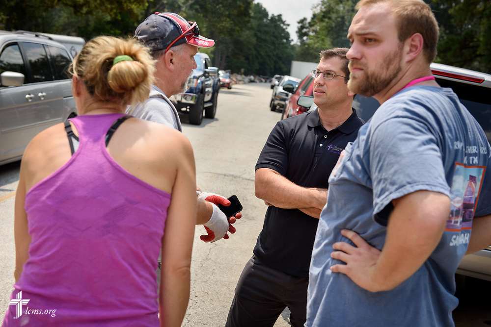 The Rev. Dr. Ross Johnson, director of LCMS Disaster Response, joins the Rev. Lee Hopf (right), associate pastor of Trinity Klein Lutheran Church, Spring, Texas, as they talk to Hurricane Harvey victims on Saturday, Sept. 2, 2017, in Spring. LCMS Communications/Erik M. Lunsford
