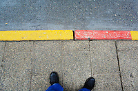 Feet and bus stop curb painted red and yellow.
