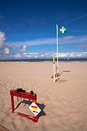 on the beach in Domburg on the peninsula Walcheren, hammer to rent for fixing the wind breaks, first aid flag, Zeeland, Netherlands.<br /> <br /> am Strand bei Domburg auf Walcheren, Verleih von Haemmern zum Befestigen der Windschutzsegel, Erste-Hilfe Flagge, Zeeland, Niederlande.