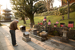 Asia, Japan, Honshu island, Nara, man praying at outdoor Buddhist shrine at Kofukuji Temple, a U.N. World Heritage Site