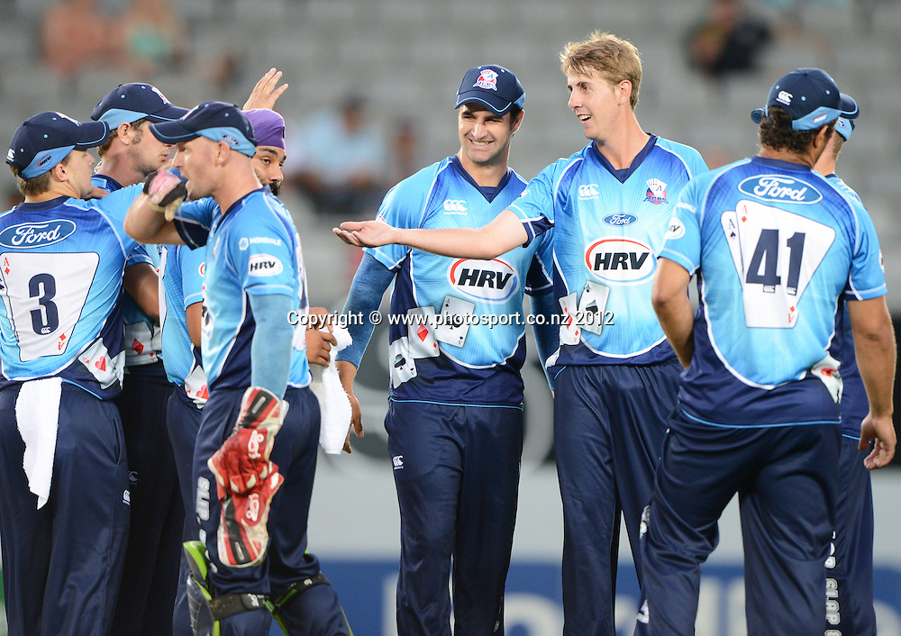 Matt Quinn celebrates with team mates the dismissal of Jesse Ryder during the HRV Cup Twenty20 Cricket match between Auckland Aces and Wellington Firebirds at Eden Park on Friday 28 December 2012. Photo: Andrew Cornaga/Photosport.co.nz