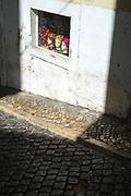 F'igures in a window and narrow sidewalk calcada in Lisbon, Portugal