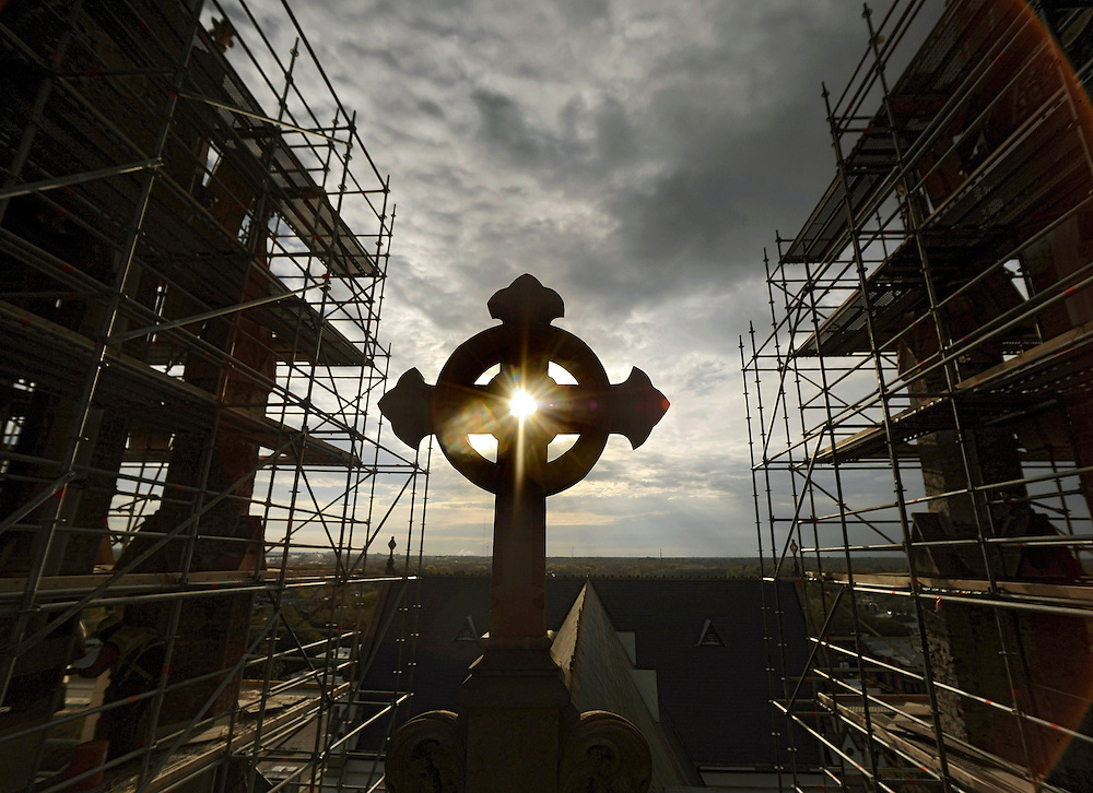 HOLD FOR RUSS BYNUM STORY- The morning sun rises through a large celtic cross over the nave of the historic Cathedral of St. John the Baptist while workers climb scaffolding to repair the 137-year-old brick steeples, Friday, March 22, 2013 in Savannah, Ga. Deep cracks where discovered between the bricks that form the towering twin steeples and is expected to cost the Roman Catholic Diocese of Savannah about $1.5 million to fix.  (AP Photo/Stephen Morton)
