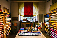 """FLORENCE, ITALY - 26 OCTOBER 2018: Ermisino fabrics are displayed here in the showroom of the Antico Setificio Fiorentino, an ancient silk mill in central Florence, Italy, on October 26th 2018.<br /> <br /> The Ermisino is an icon fabric of the ancient silk factory, a special type of Renaissance shot taffeta made with threads of different colours, so as to have tones that are shimmering and fluid like a cascade of light. Woven in three classic weights (leggero, scempio and doppio), for centuries it was the distinctive mark of the most illustrious nobility.<br /> <br /> The showroom of the Antico Setificio Fiorentino displays  many of the 100 different kinds of fabric the mill can produce, with vignettes of them turned into pillows, sofas and curtains.<br /> <br /> Fabrics are priced accordingly, starting at about 200 euros a meter and going as high as 2000 euros a meter for lampasso, a special kind of damask so labor intensive to produce only 20 centimeters can be made a day. There are brocades, jacquards, damasks, shantung, satin, moire, rustic filaticcio and stiff, shimmering ermisino. The palette extends from pure """"panna"""", or cream, to delicate pastels and rich jewel tones, often shot with threads of gold or silver.<br /> <br /> The Antico Setificio Fiorentino is a silk mill, located in central Florence within view of the old city walls in the San Frediano neighborhood, that produces the kind of fabrics destined for city palaces and country estates. The mill was bought in 2010 by Stefano Ricci from the Pucci, with an eye to using it to produce fabrics for the launch of a new home collection<br /> <br /> Lined up in rows are the dozen looms that take the slender threads, by now dyed emerald and ruby and sapphire, and weave them into the textiles that form a part of the fabric of Florentine life.<br /> <br /> Silk was made in the city as far back as the 1300s, a commodity to trade for precious materials. In more recent times, the fabric in the gowns in """"Il Gattopar"""