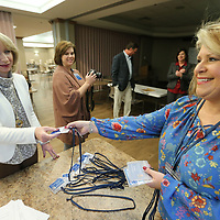 Melinda McCrory, left, gets her new ID badge from Angie Weaver Friday as employees in AMory begin the transition to becoming part of the North Mississippi Medical Center network.