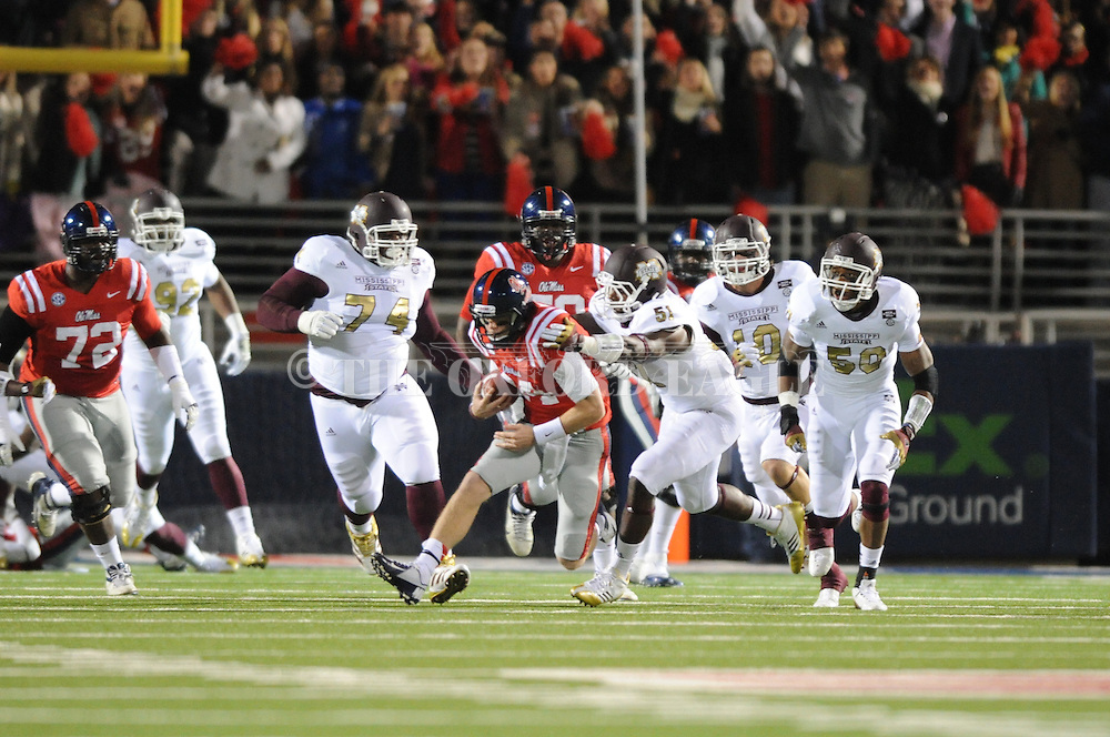 Ole Miss quarterback Bo Wallace (14) runs vs. Mississippi State linebacker Deontae Skinner (51) at Vaught-Hemingway Stadium in Oxford, Miss. on Saturday, November 24, 2012. Ole Miss won 41-24.