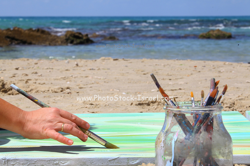 painters hands as they paint a seascape on the beach