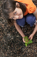 Portrait of girl (7-9) planting black locust tree